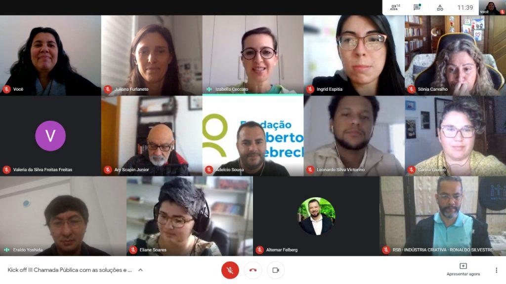 A imagem mostra pessoas em uma reunião do Zoom. Algumas sorriem, enquanto outras parecem estar falando.